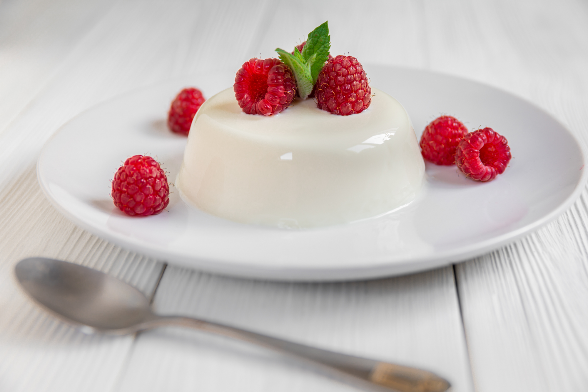 Panna cotta with raspberry, decorated with fresh mint on a white background